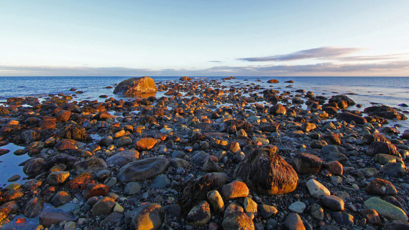 A line of boulders on a tidal shoreline extend out into the Barents Sea.