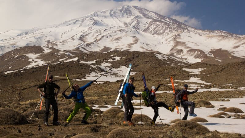 Photo of Mount Damavand in distance with five team members in foreground wearing skis on their backs and throwing funny poses.