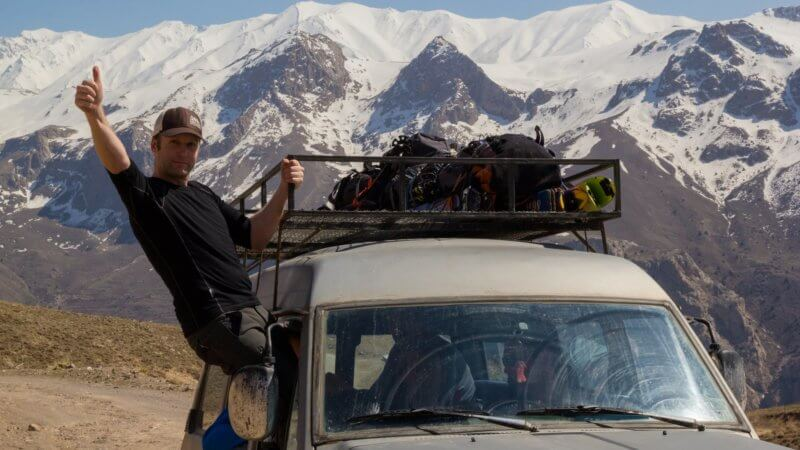 Chris hanging out the side window of a 4x4 giving a thumbs up. Snow covered mountains in the background.
