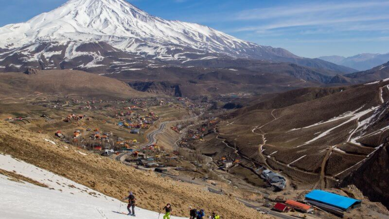Photo of Mount Damavand in background and five ski mountaineers on a nearby peak in foreground. In the middle is a very wide valley with a few dozen houses.