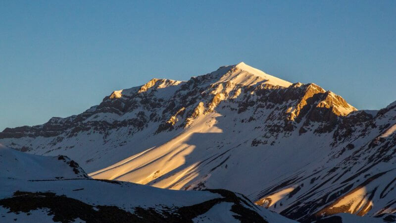 A far shot of a morning sunrise over an unnamed alpine peak that has a long, wide band of rock.