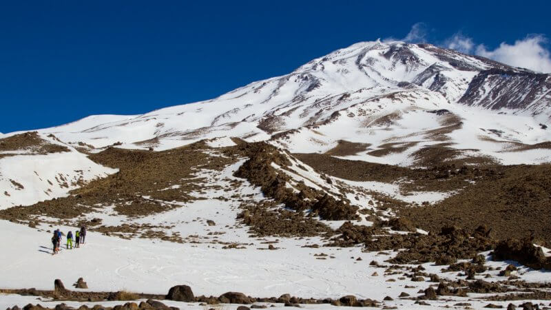 A Mount Damavand photo showing four ski mountaineers heading towards the cloudless summit.