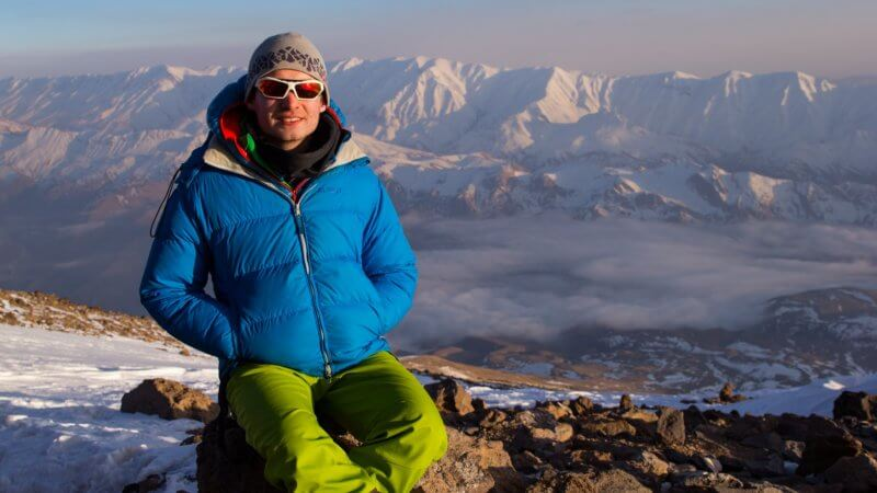 George wearing a blue jacket and green ski trousers poses for a sunset photograph.