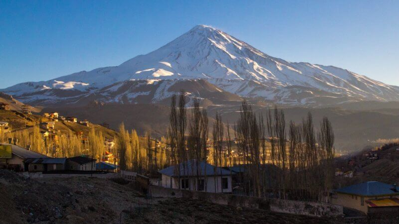 An early morning Mount Damavand photo, taken from a few miles away. A few houses are in the foreground and the sun is slowly creeping into the valley.