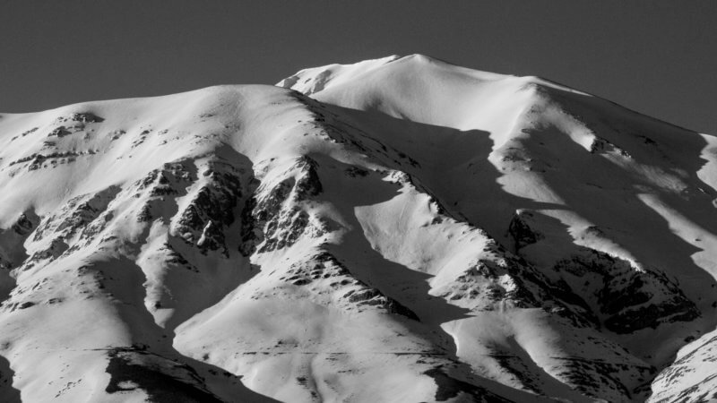 A black and white photo of a snow covered mountain. At the bottom of the image is very faint outline of a remote mountain road cutting along its slopes.