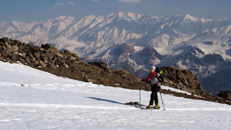Shirin photographed on Mount Damavand, skiing uphill towards a mountain hut in Iran. A long chain of snowy mountains in background.