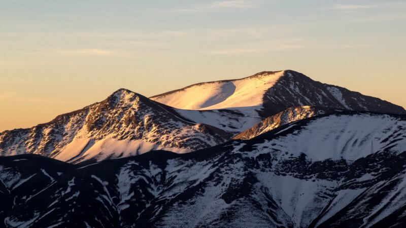 A golden sunset on a snowy Iranian peak.