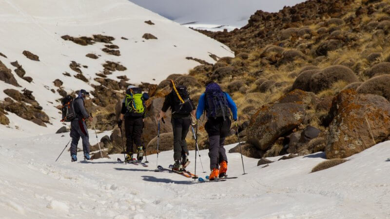 Four people skiing up a small valley on Mt. Damavand. Snow is on the left and bare rock and earth on the right.