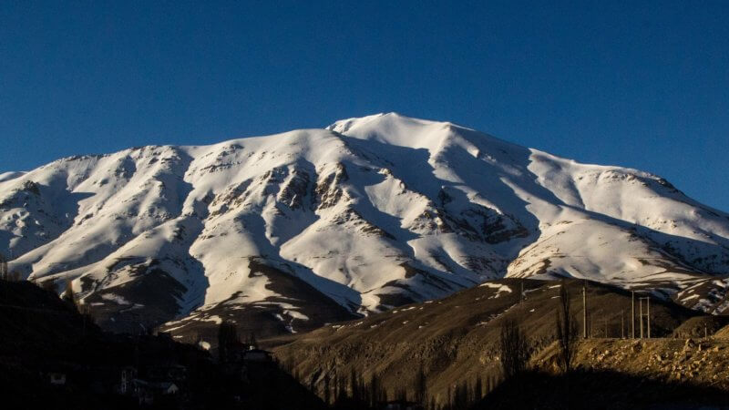 A far shot of a snowy mountain on a clear day in Iran.