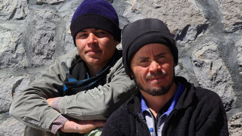 Two Afghan porters sat outside a Damavand mountain hut, smiling for the camera.