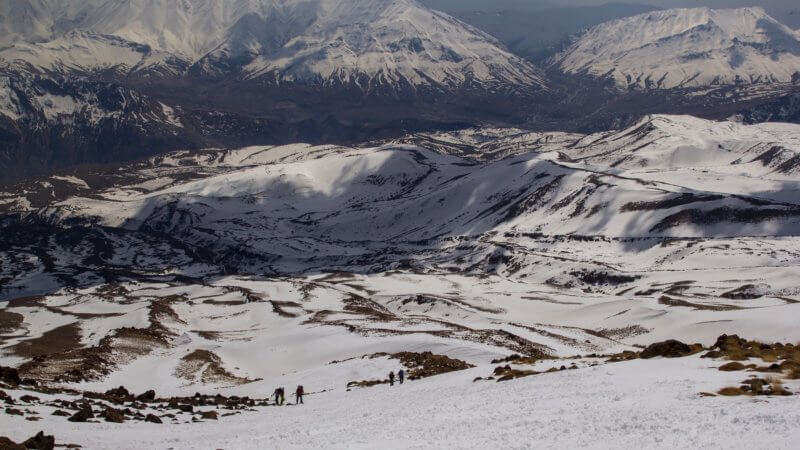 A photo on Mount Damavand's slopes showing a wide view of four people skiing uphill.