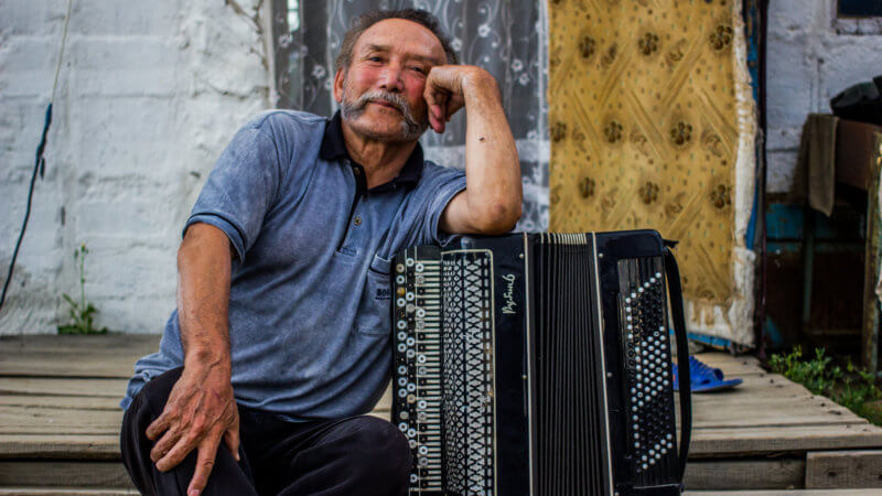 A Tuvan musician with handlebar moustache coolly leaning against his accordion.