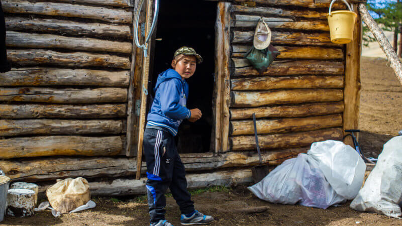 A Tuvan boy wearing athletic clothing leaning on the door of a log mountain hut.