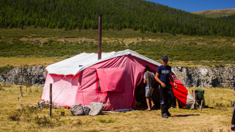 A nomad family's pink coloured tent with stove pipe coming out the roof.