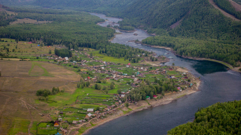 A photo of the Yenisei River from a high mountain point, with an Old Believer village beside it.