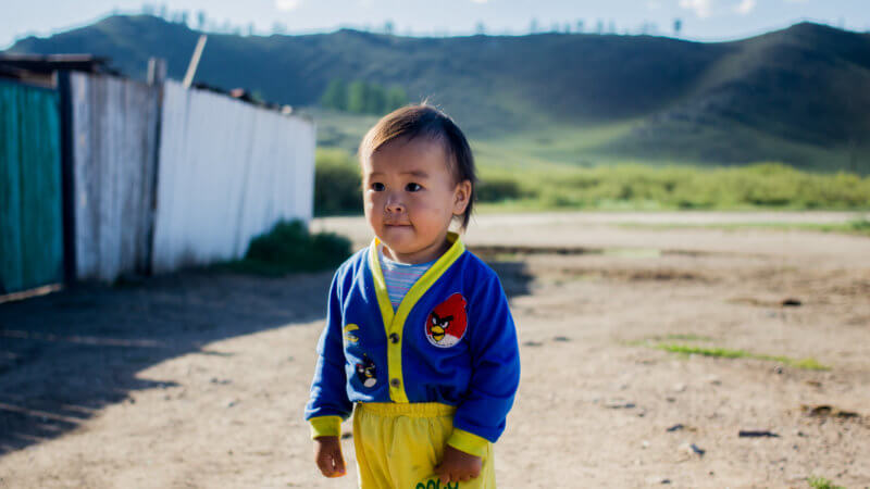 A little Tuvan boy with yellow shirts and blue sweater.