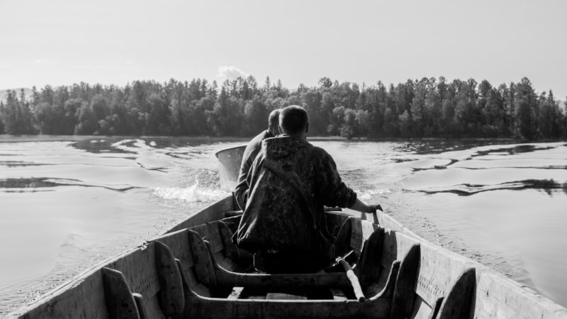 Black and white image sat in a wooden longboat in Azas Lake.