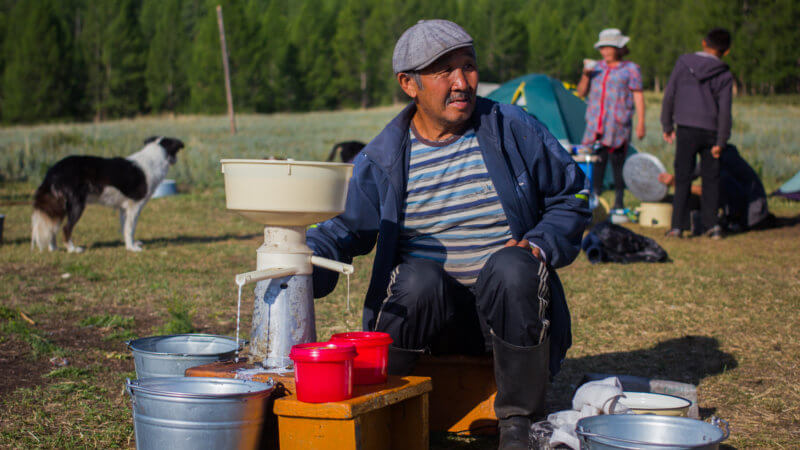 A Tuvan farmer crouched down next to a hand-crank milk pasteurising machine.