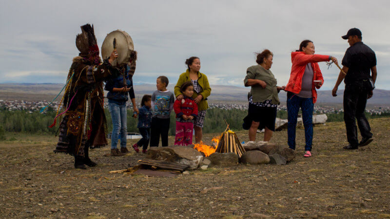 A traditional shamanic ceremony with a shaman beating a drum around a fire.