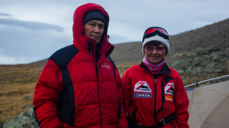 Two Tuvan mountaineers in red clothing at their campsite near Munghulik.