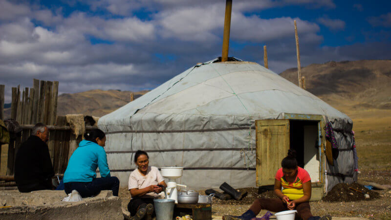 A Tuvan family sat outside of their yurt doing daily chores.