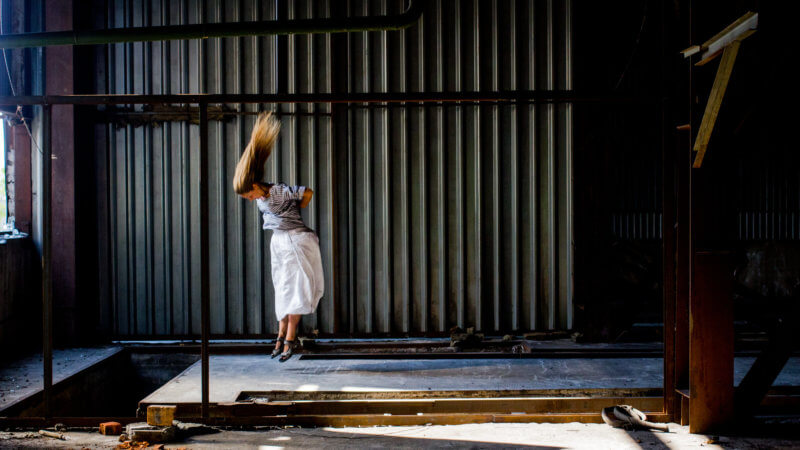 An experimental image of a dancer with a white dress jumping in the air, inside of an industrial unit.