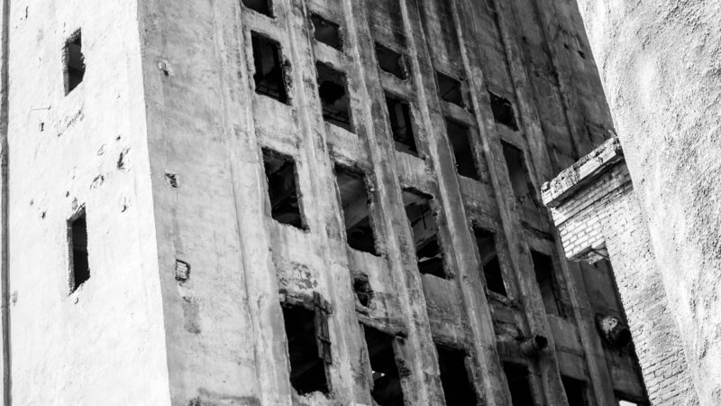 Black and white photo of an abandoned bread factory with destroyed windows.