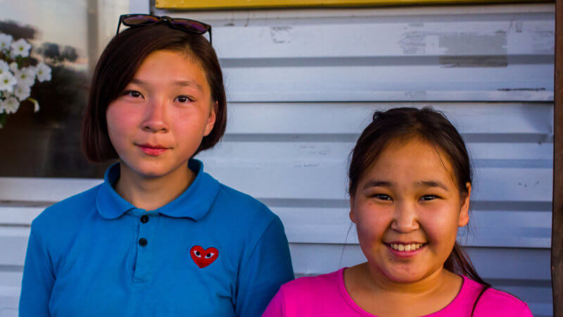 Two happy looking girls smiling for the camera, wearing pink and blue t-shirts.