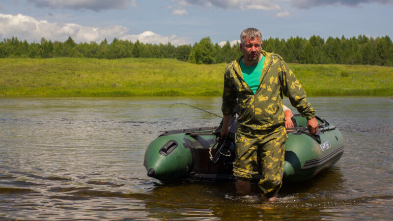 A white Russian hunter in camouflage tows a green inflatable to the shoreline.