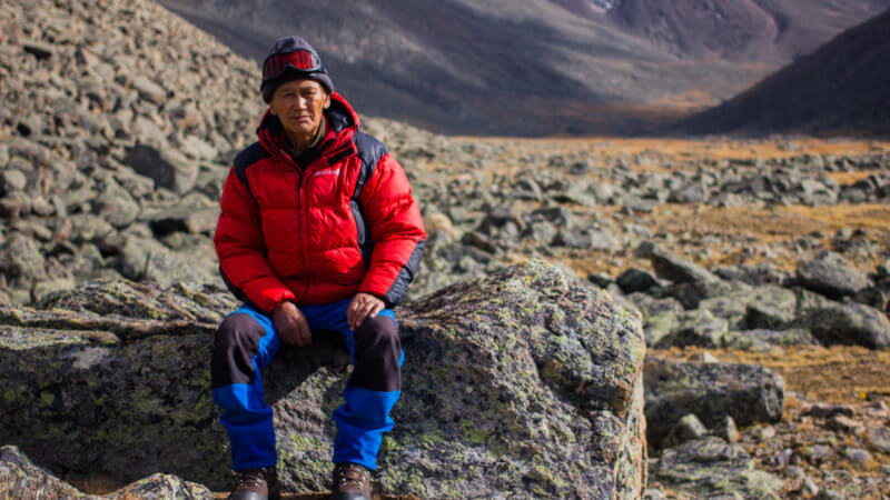 A Tuvan mountaineer wearing blue trousers and red jacket sat on a rock posing for the camera.