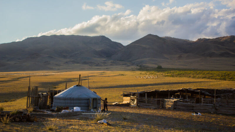 A yurt and wooden goat pen with a sloping, sun-kissed plateau in the distance.