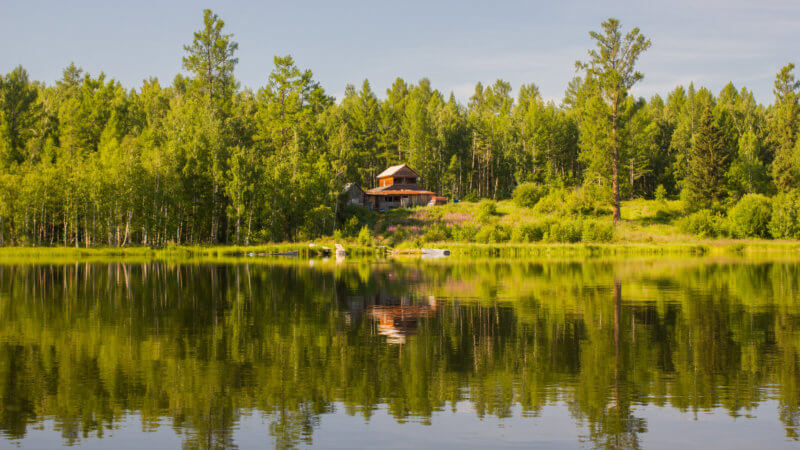 A two-floored house tucked away in a green forest overlooking Azas Lake.