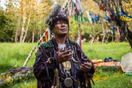 A shaman in traditional clothes with his eyes closed speaking to the forest spirits.