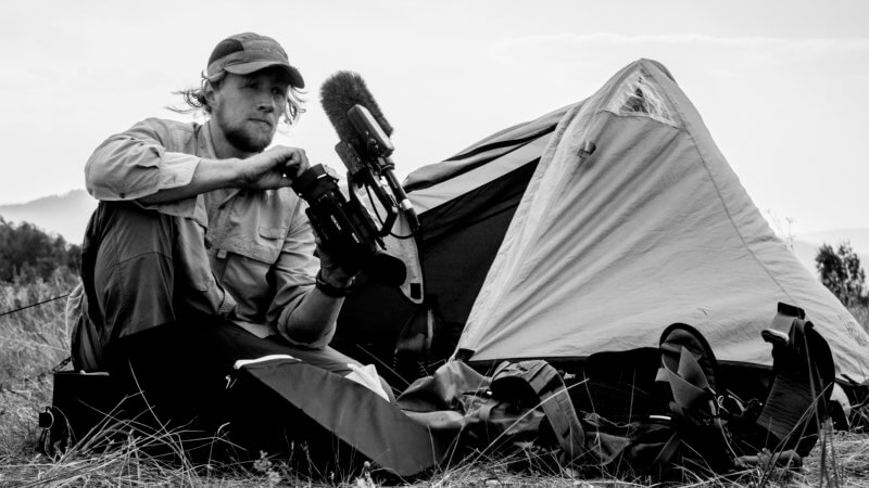 Black and white photo of a cameraman crouched beside his tent and fiddling with the lens.