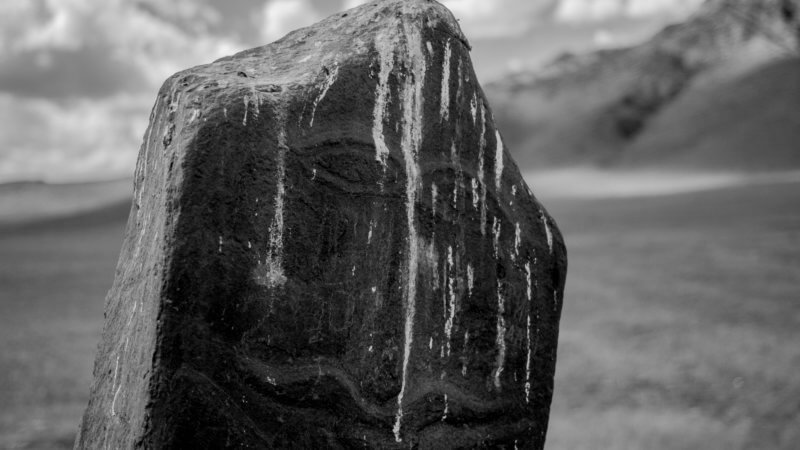 Black and white photo of a Scythian-era standing deer stone in Tuva with a moustached faced carve on it.
