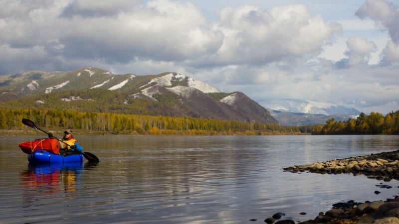 A man paddling a blue packraft descends the Yenisei River with snow-covered mountains behind.