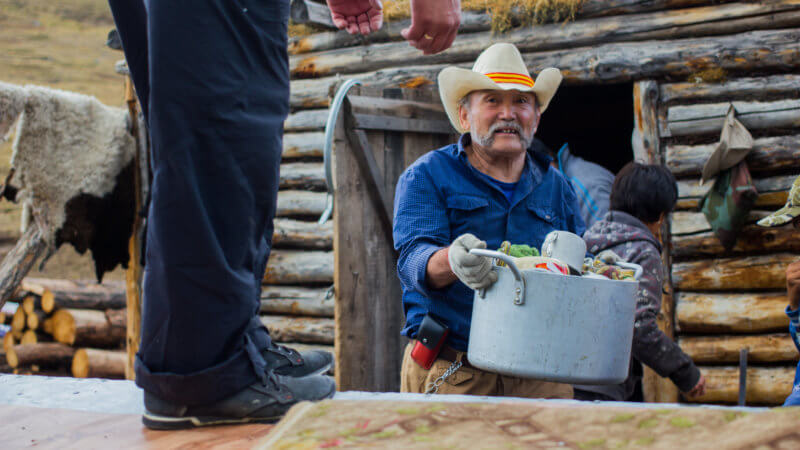 A Tuvan guy wearing a cowboy hat and holding a pot outside of a wooden hut.