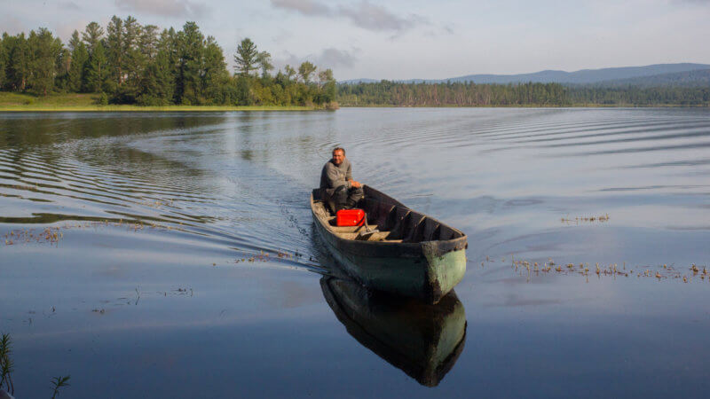 A white Russian man approaches an island in a motorised longboat in Azas Lake, Tuva.