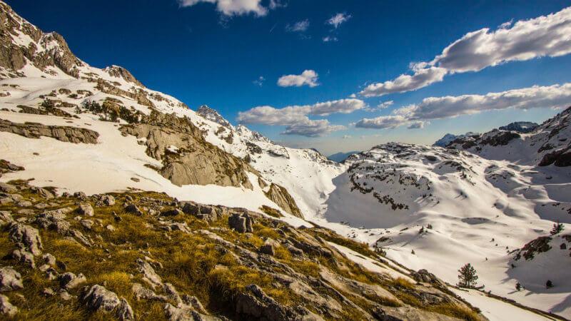 Wide angle shot of a limestone plateau with deep snow covered bowls.