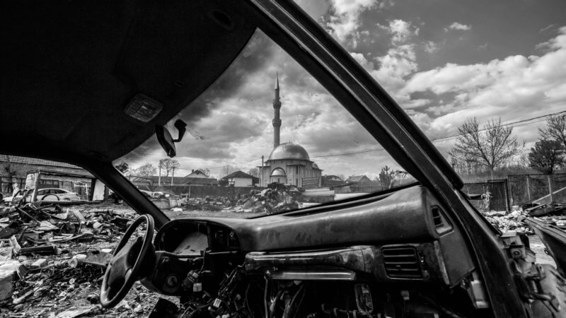 Kosovo mosque framed through the windshield of an abandoned car.
