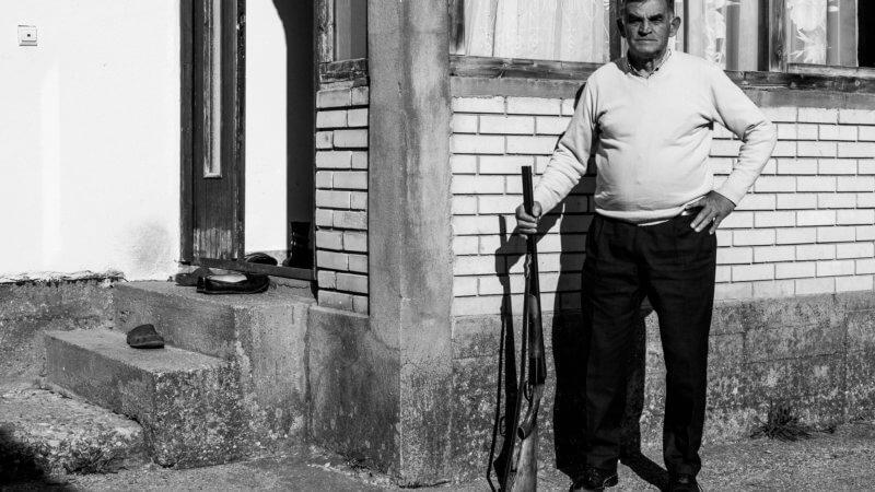 Black and white image of Montenegro man posing with his shotgun.