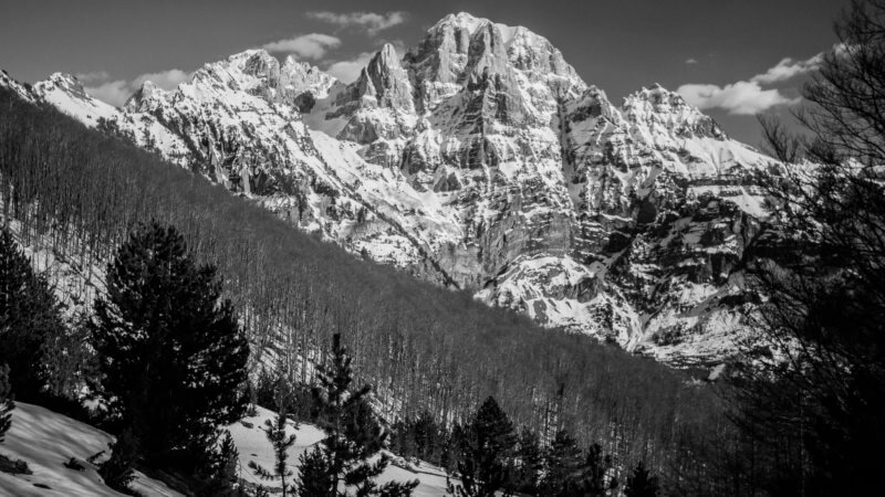 Black and white photo of a giant snow-covered mountain in the Dinaric Alps.
