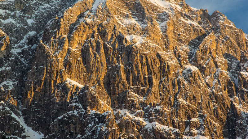 Close up photo of jagged limestone mountains dusted in powder snow.