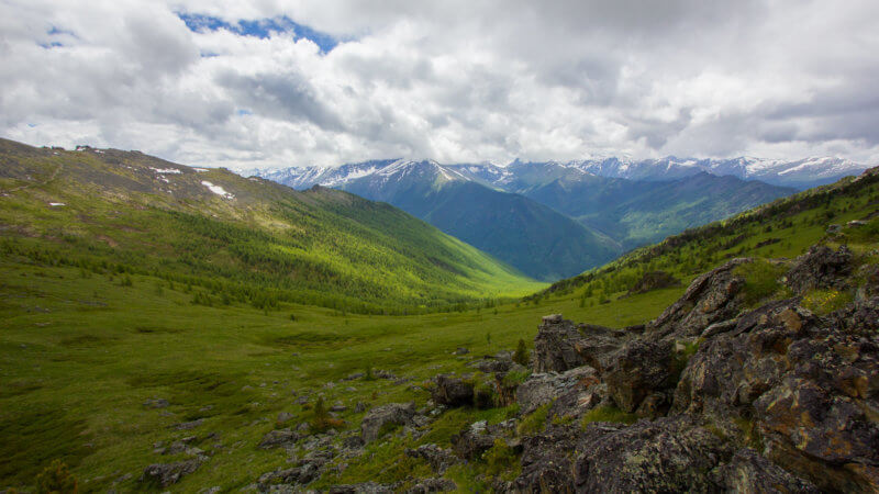 A wide view of an alpine valley shot from a rocky outcrop in the Altai.