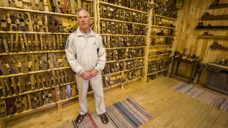 A man in a white track suit stands in front of the world's largest collection of hand planes.