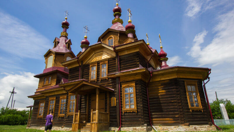 A traditional wooden Russian orthodox church with multiple spires and crosses.