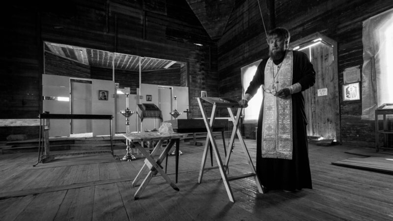 Black and white photo of an orthodox priest performing a ceremony inside of a church.