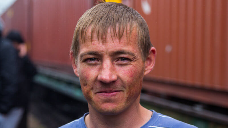 A young Russian man with a weathered face and kind smile in front of a red cargo train carriage.