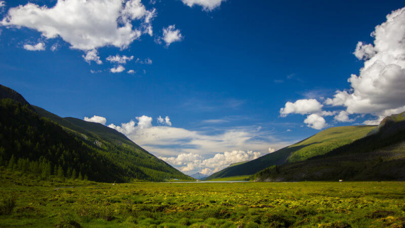 Wide view of green alpine valley beneath puffy white clouds and bright blue sky.