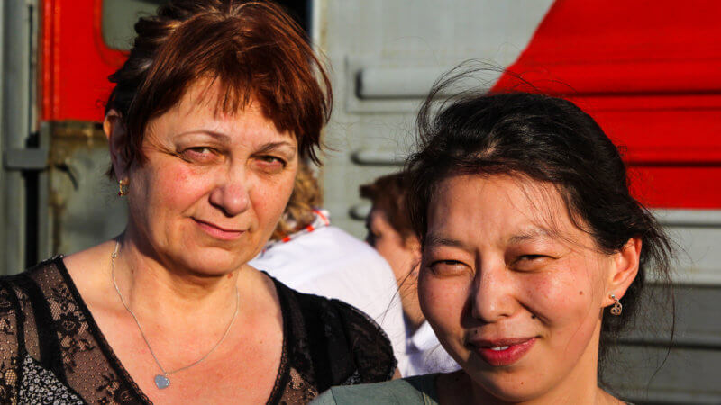 A white Russian and Mongolian woman pose for a photo in front of a train.